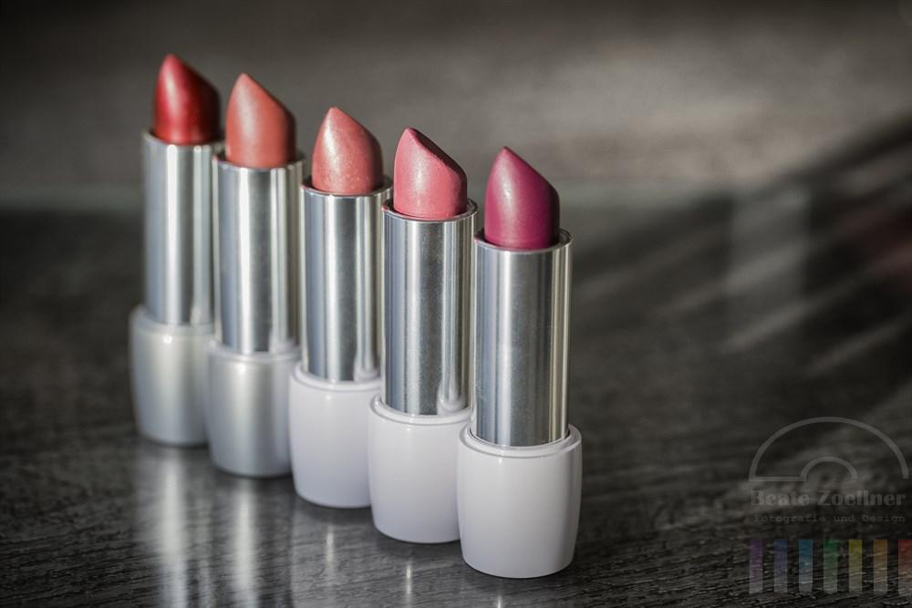 fünf nebeneinander stehende Lippenstifte in verschiedenen Rottönen