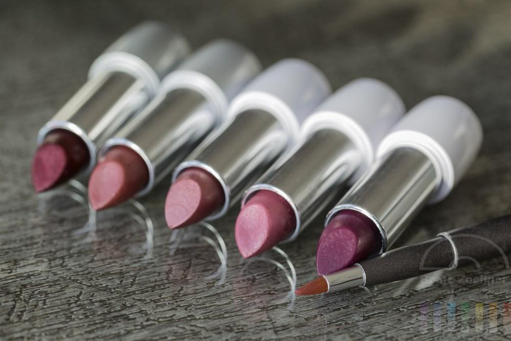 fünf nebeneinander liegende Lippenstifte in verschiedenen Rottönen und ein Pinsel