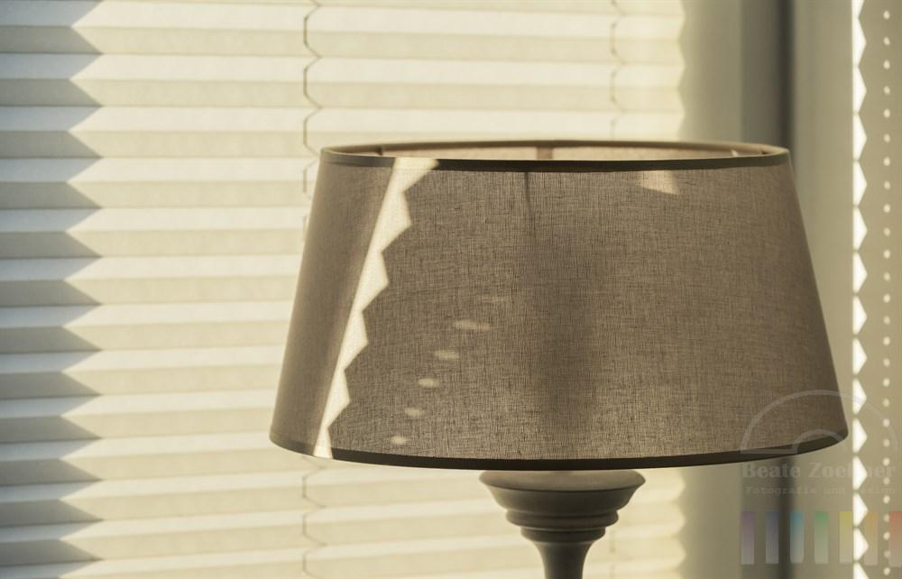 Sonnenlicht fällt durch ein Fenster und malt Zackenmuster auf Jalousie, Lampenschirm und Zimmerwand.