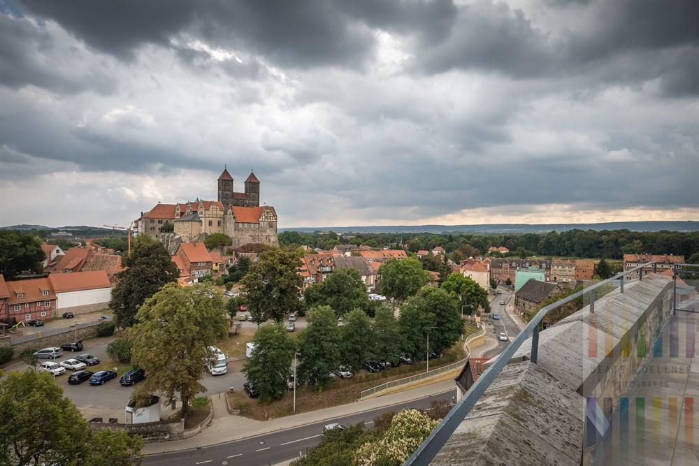 Blick vom Münzenberg auf die Altstadt und den Schlossberg der UNESCO-Welterbe-Stadt Quedlinburg mit Stiftskirche. Über der Stadt hängen bleigraue Regenwolken