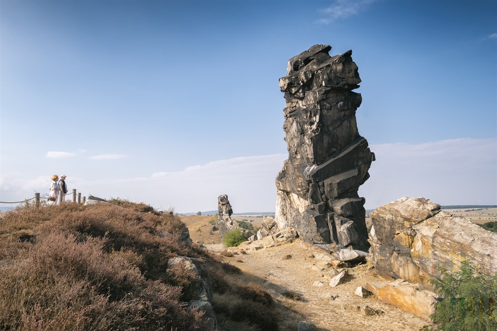 Urlauber bestaunen die bizarre Sandsteinformation der Teufelsmauer bei Weddersleben, sonnig