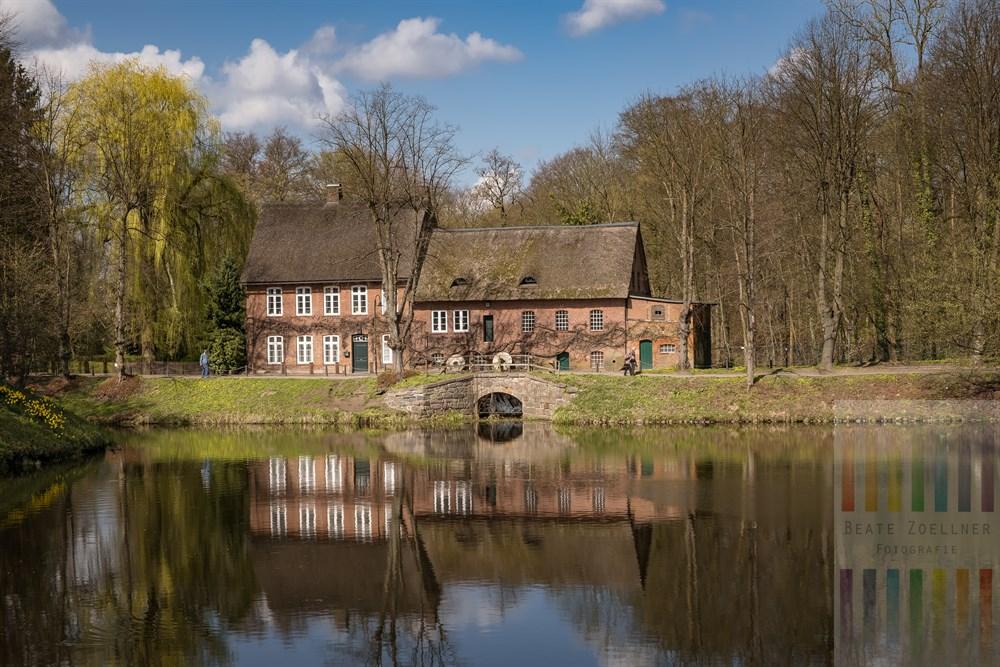 Das denkmalgeschützten Gebäude der alten Wassermühle im Ahrensburger Schosspark spiegelt sich im Wasser des Teiches, frühlingshaft