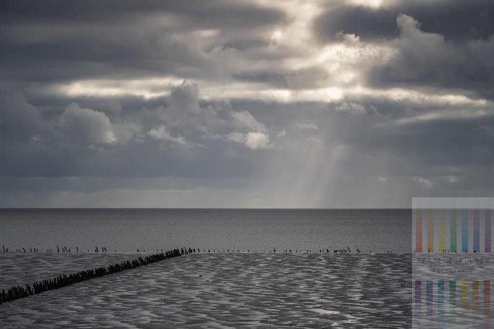 Blick vom Römö-Damm über das Wattenmeer. Lichstrahlen, die durch die Wolkendecke hindurch dringen, treffen auf den Horizont
