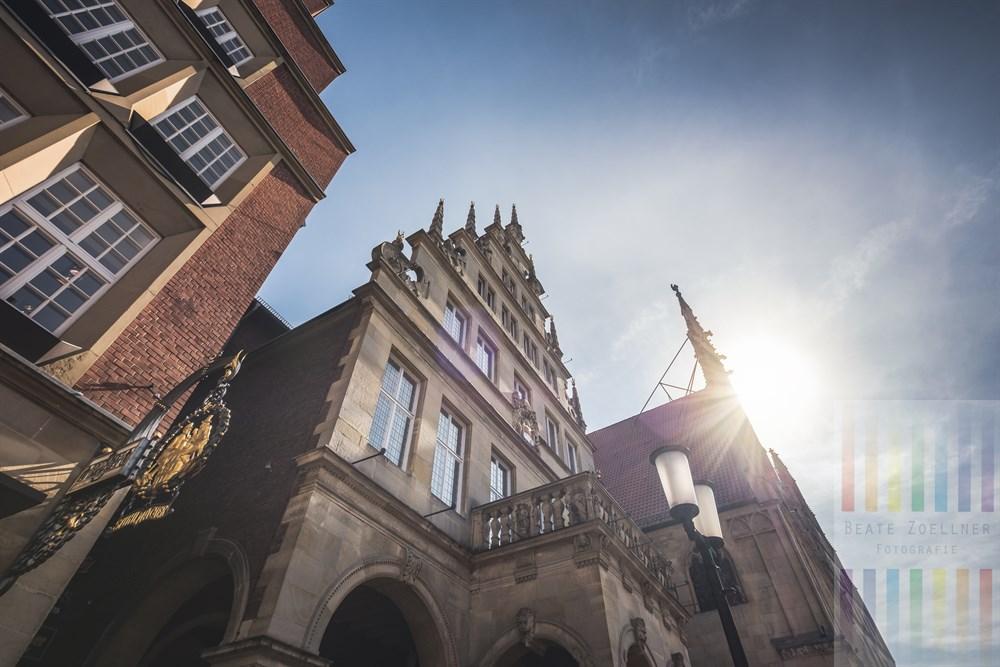 """Blick auf das Stadtweinhaus und das historosche Rathaus von Münster am Prinzipalmarkt im Gegenlicht der Frühlingssonne. Links die Traditionsgastronomie """"Stuhlmacher"""""""