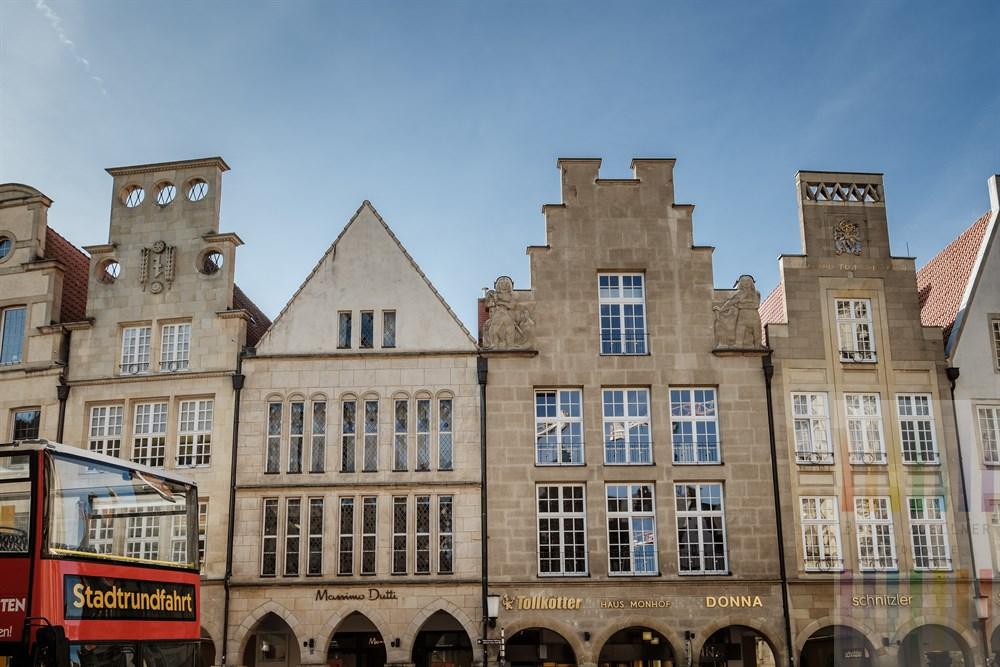Roter Doppeldecker-Bus auf Stadtrundfahrt hält vor den historischen Häusern am Prinzipalmarkt in Münster