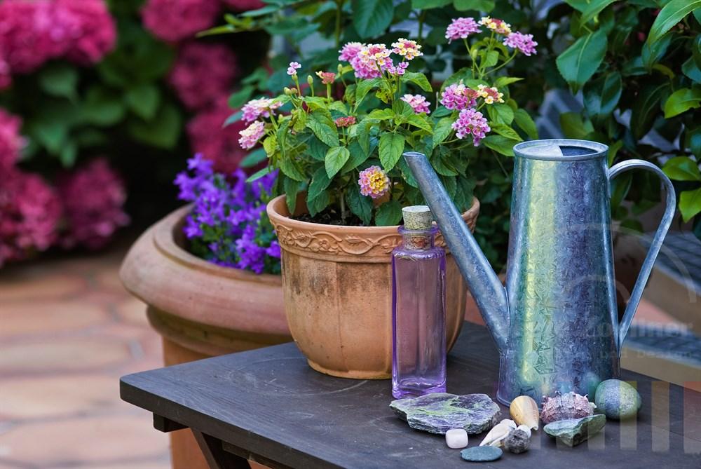 Liebevolle Dekorationsgegenstände auf einem kleinen Tisch bilden ein Stillleben auf einer sommerlichen Terrasse