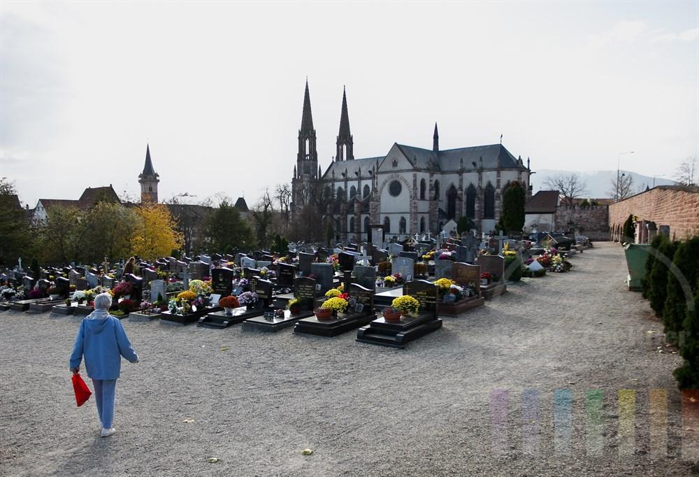 Besucherin geht auf den Friedhof in Obernai/Elsass. Im Hintergrund die Kirche St. Peter und Paul