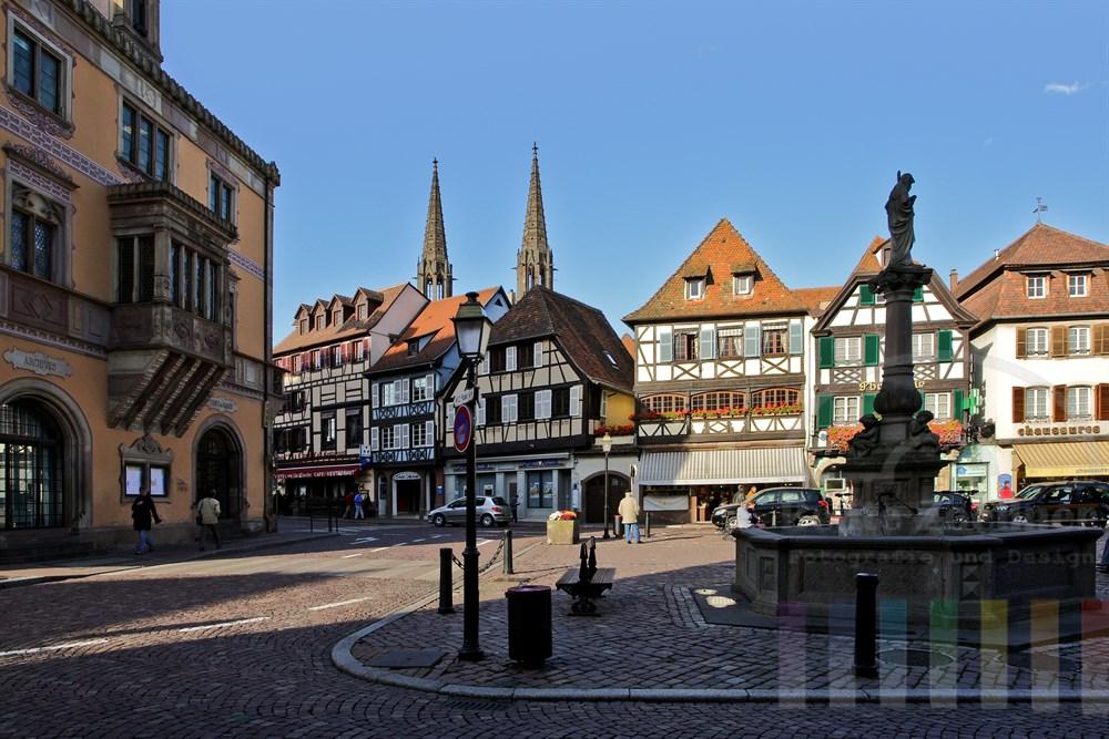 Marktplatz in der historischen Altstadt von Obernai/Elsass mit Brunnen und Rathaus (links). Im Hintergrund die Türme der St. Peter und Paul Kirche.