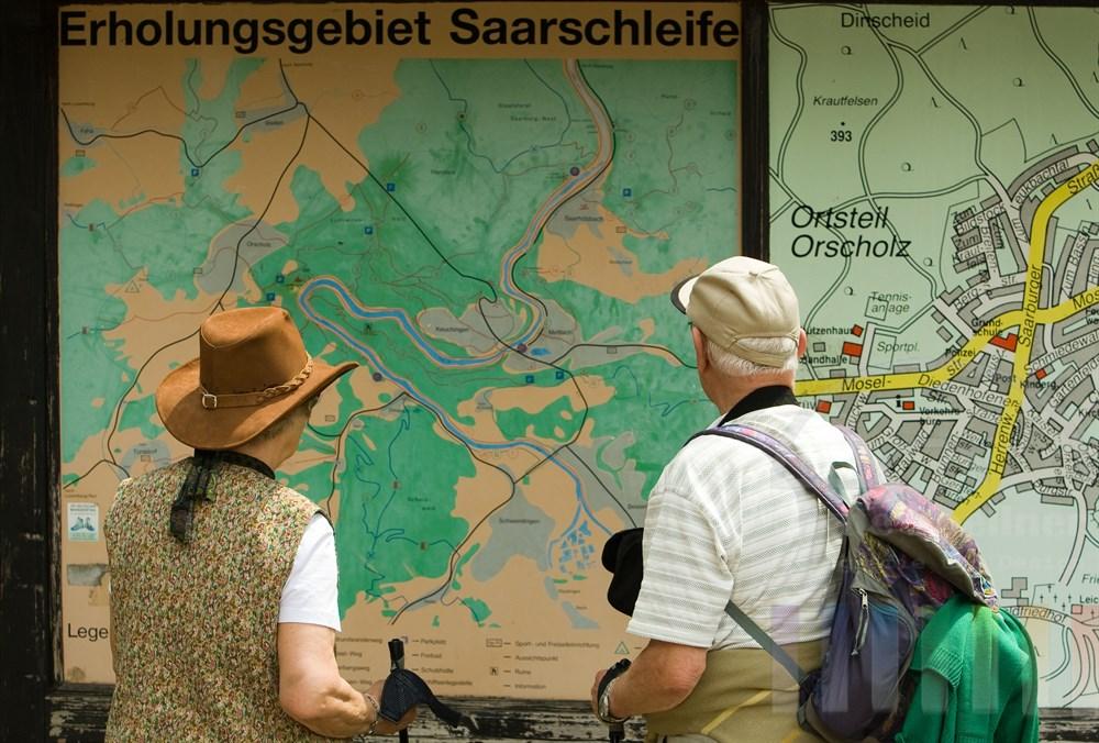 Rentnerpaar in Wanderkleidung steht studierend vor einer großen Tafel, die eine Karte des Naherholungsgebietes Saarschleife zeigt