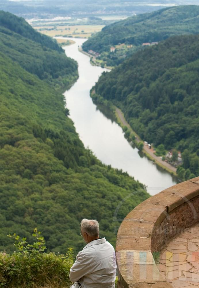 Renter sitzt am Rande der Aussichtsplattform über der Saarschleife bei Coelf und geniesst den Ausblick in die Landschaft