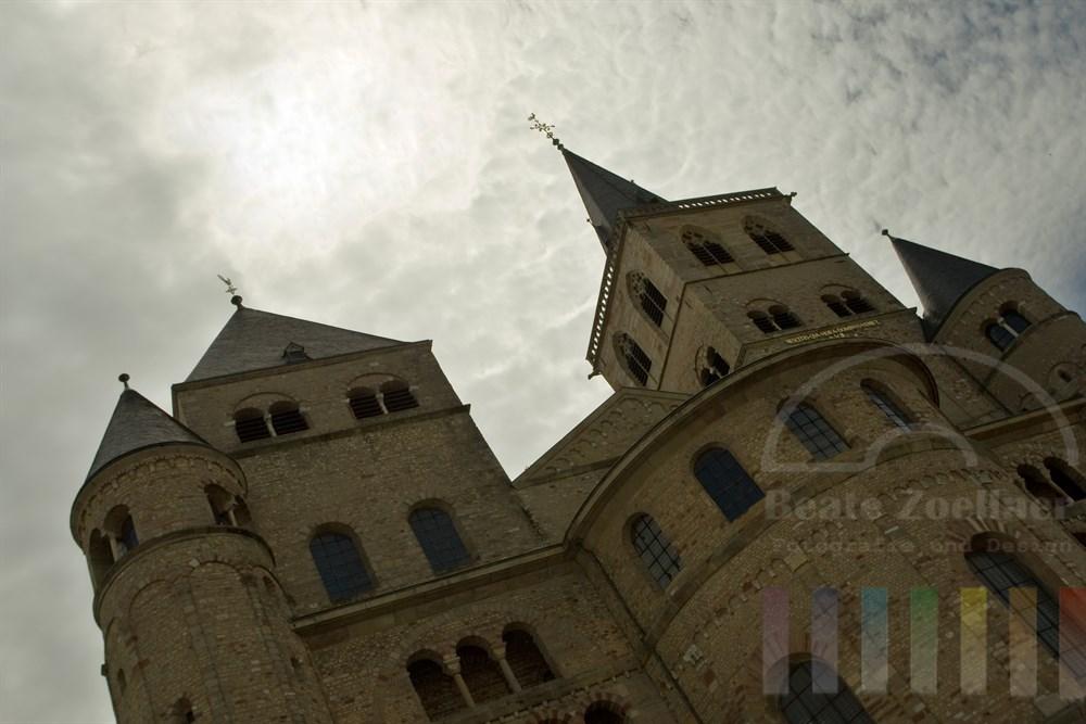 Der Dom zu Trier unter bewölktem Himmel, die Sonne steht jedoch erkennbar direkt über dem Bauwerk, das zum UNESCO-Weltkulturerbe zählt