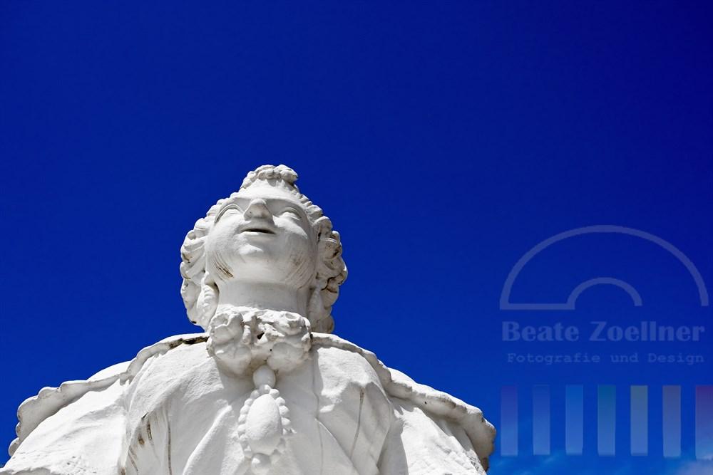 weisse Rokoko-Skulptur auf der Terrasse des kurfuerstlichen Palastes von Trier vor blauem Himmel
