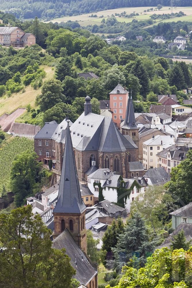 Blick von der Burgruine auf die katholische Pfarrkirche St. Laurentius (Bildmitte) im historischen Stadtkern von Saarburg, sommerlich