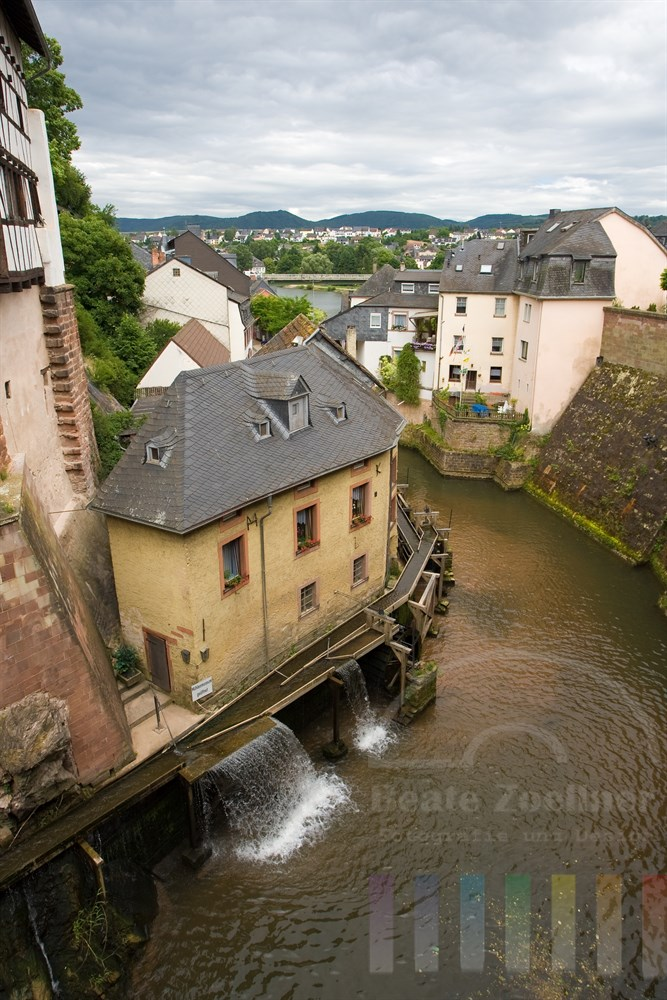 Der Leukbach in Saarburg treibt die alte Wassermühle des Mühlenmuseums an und mündet dann in die Saar (Hintergrund)