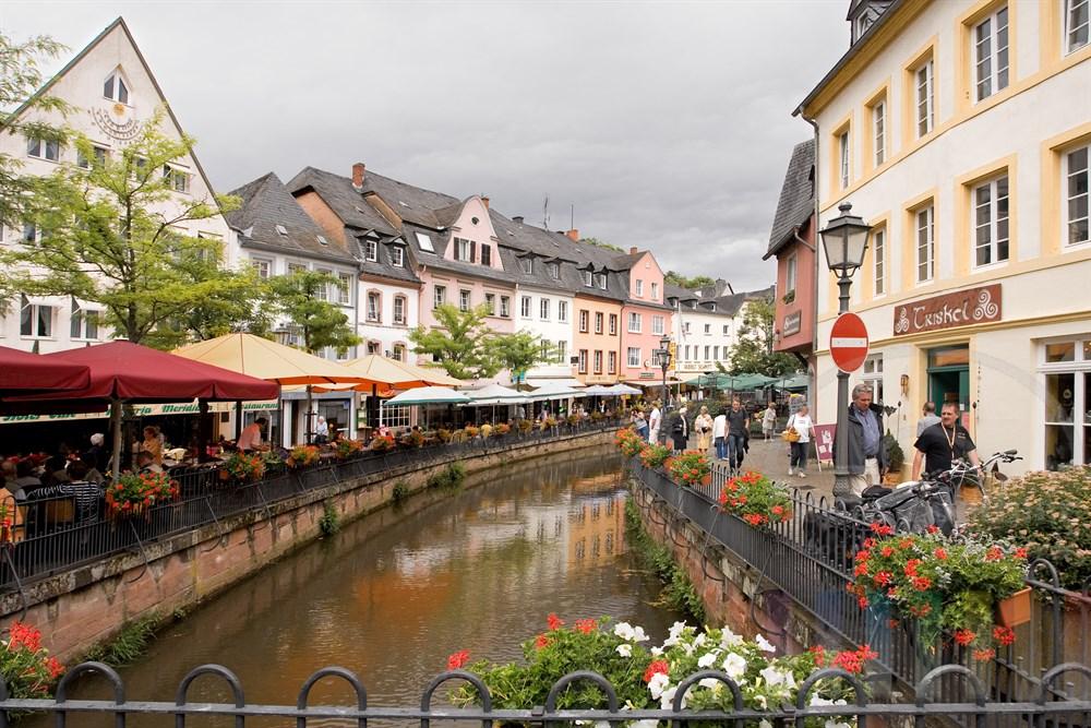 Der Leukbach fließt durch den alten Stadtkern von Saarburg. Touristen bummeln durch die Altstadt oder sitzen in den Strassencafés
