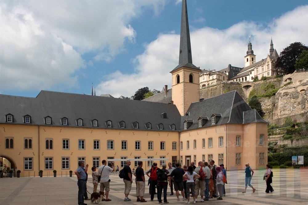 Eine Touristengruppe steht auf dem Platz vor der ehemaligen Abtei Neumünster und der St. Johanneskirche im Stadtteil Grund unterhalb der Altstadt von Luxemburg. Die Abtei ist heute Kulturzzentrum. Im rechten Gebäudeflügel ist der Sitz des nationalen Denkmalamtes