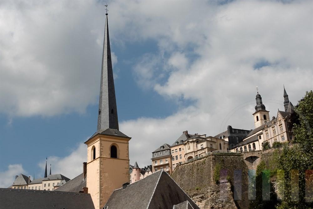 Der Turm der St. Johanneskirche in der Vorstadt Grund. Im Hintergrund die alte Festungsmauer und die Altstadt von Luxemburg