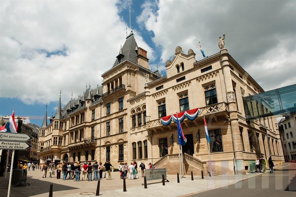 Touristengruppen stehen vor dem Palast des Großherzogs von Luxemburg und dem Abgeordneten Haus (Gebäudeflügel rechts)
