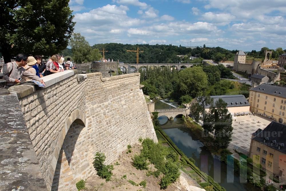 Touristen schauen über die Stadtmauer auf den Stadtteil Grund, die St. Johanneskirche und die ehemalige Abtei Neumünster (heute Kulturzentrum) am Ufer des Flusses Alzette