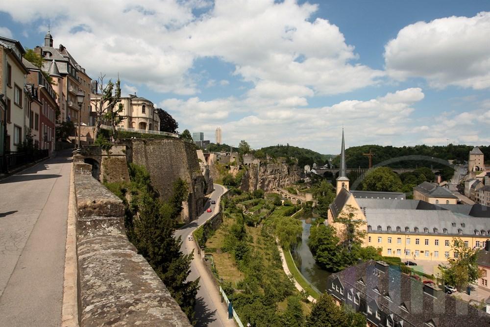 """Blick über die historische Altstadt von Luxemburg. Rechts gruppieren sich die Gebäude der Vorstadt """"Grund"""" und die Sankt Johanniskirche  am Ufer des Flusses Alzette"""
