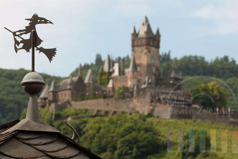 Hexenfigur aus Metall reitet auf einem Besen. Die Figur ziert ein Hausdach in Cochem an der Mosel - im Hintergrund thront die Reichsburg auf einem Hügel