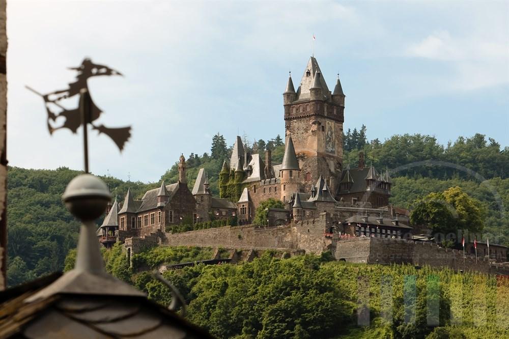Die Reichsburg thront über der Stadt Cochem an der Mosel. Das Foto entstand vom anderen Moselufer aus. Im Vordergrund reitet eine kleine Hexenfigur aus Metall auf ihrem Besen als Schmuck auf einem Hausdach