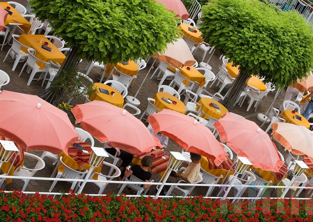 Menschen sitzen unter Sonnenschirmen auf der Terrasse eines Gartenlokales