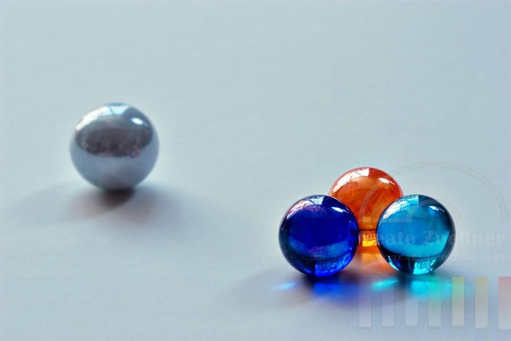 Symbolfoto, tabletop: drei farbige Glasmurmeln liegen zusammen, eine farblose Glaskugel liegt allein im Hintergrund, Hintergrund: graublau