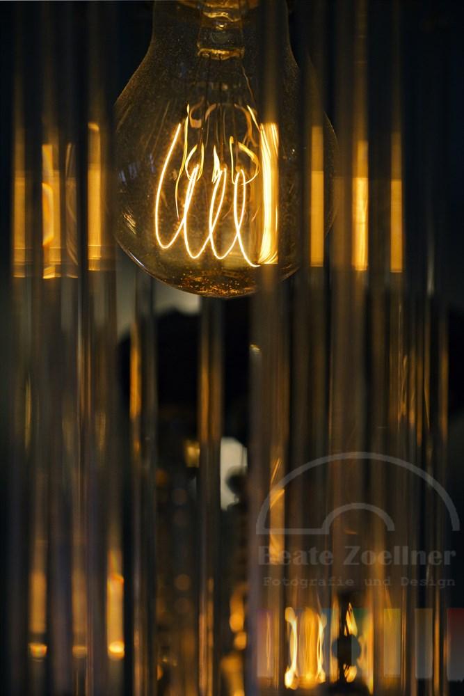 historische Deckenlampe mit Gluebirne und herab haengenden Glasstaeben, in denen das Licht reflektiert