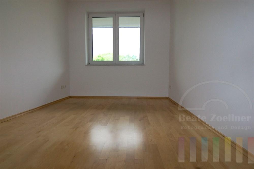 schmales, leeres Zimmer, Licht fällt durch ein Doppelfenster auf den hellen Parkettboden