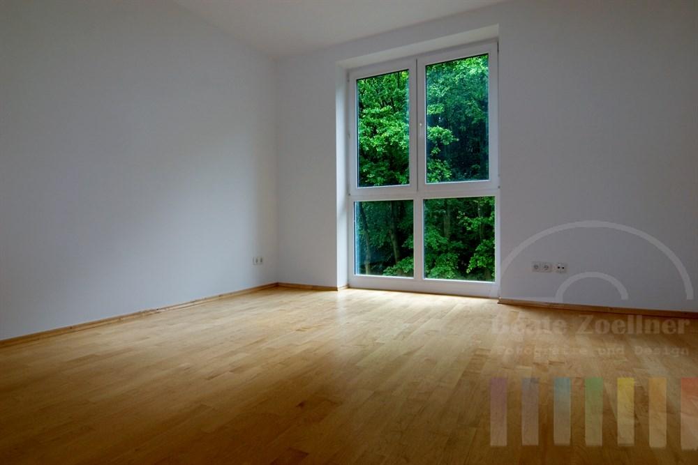 leeres Zimmer einer Wohnung mit Blick durch das Fenster ins Grüne. Boden: Parkett, Wände weiss