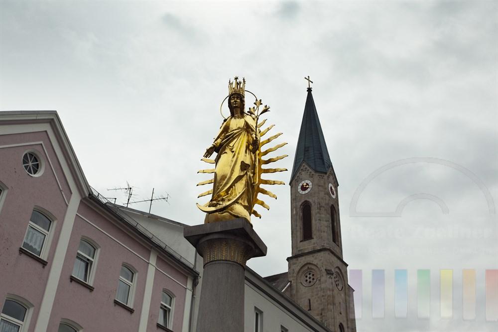 Goldene Marienfigur auf dem Marktplatz von Walkdkirchen im Bayerischen Wald. Im Hintergrund der Kirchturm