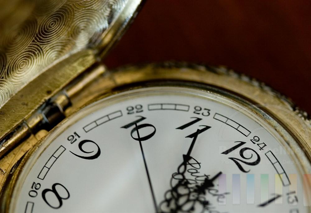 Makro, Nahaufnahme: Detail einer alten Taschenuhr, Zeiger auf kurz vor 12 Uhr, Deckel  und Rand etwas angelaufen, glänzen golden, Hintergrund dunkelbraun durch dunkles Holz