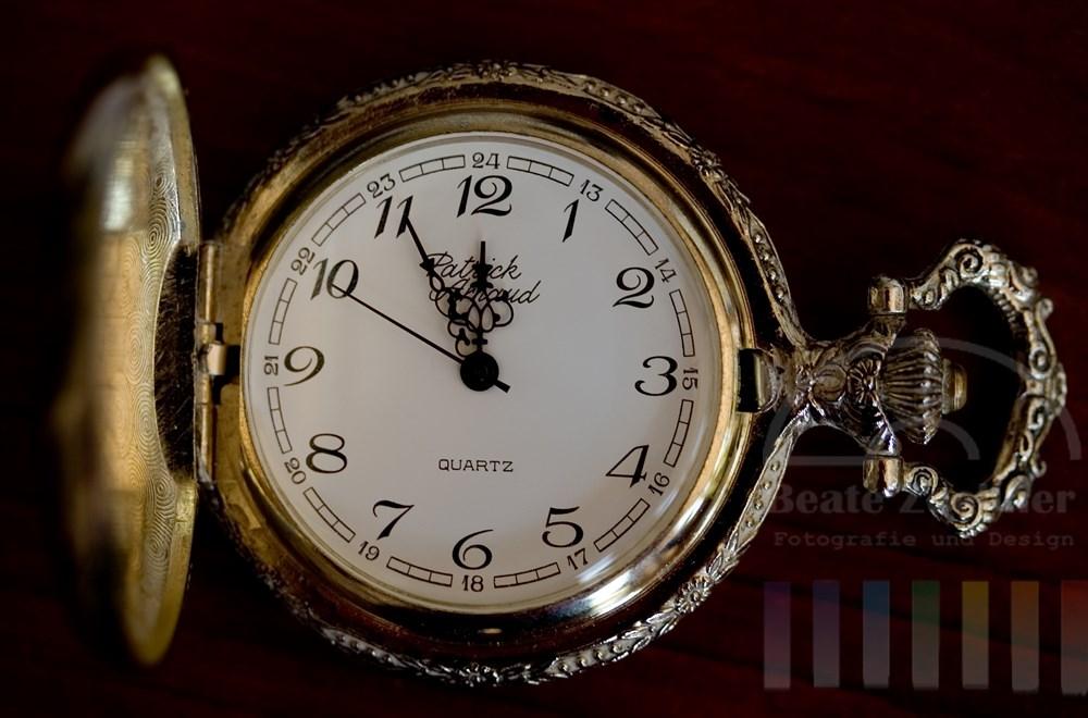 alte Taschenuhr, silberner Deckel ist aufgeklappt, Uhrzeiger zeigen auf kurz vor 12 Uhr, Hintergrund dunkles Holz