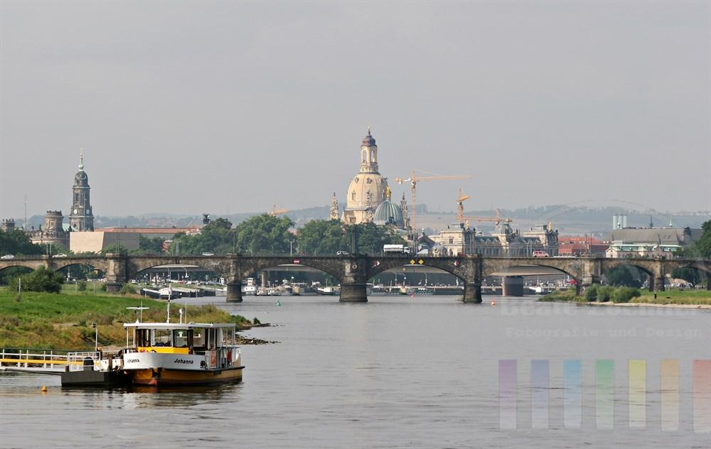 Blick auf die Stadt Dresden, deren Brücken und Silhouette von einem Elbdampfer aus. Baukräne und restaurierte Frauenkirche in der Bildmitte