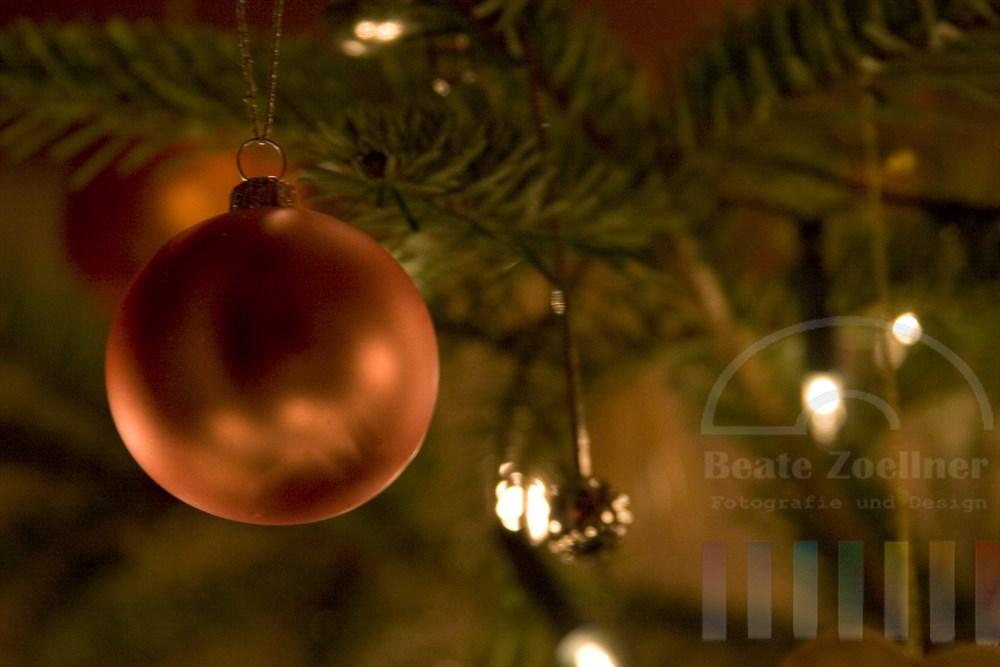 close: matt glänzende Weihnachtsbaumkugel am Baum hängend, warmes Umgebungslicht