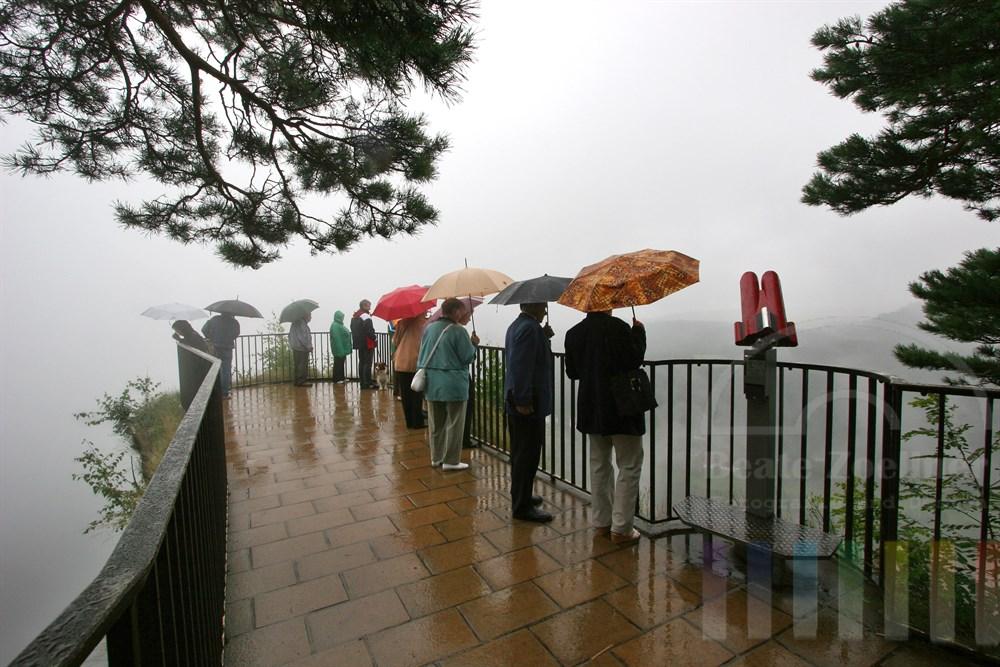 Touristen mit bunten Regenschirmen und in Regenbekleidung stehen auf Aussichtplattform am Gitter. Zweige einer Kiefer neigen sich vom linken Bildrand über die Plattform. Am Rand des Aussichtspunktes steht ein ungenutztes Fernglas. Der Hintergrund ist eintönig grau durch Nebel und Regenschwaden. Das Foto entstand in der sächsischen Schweiz, im Elbsandsteingebirge, Nähe Bastei