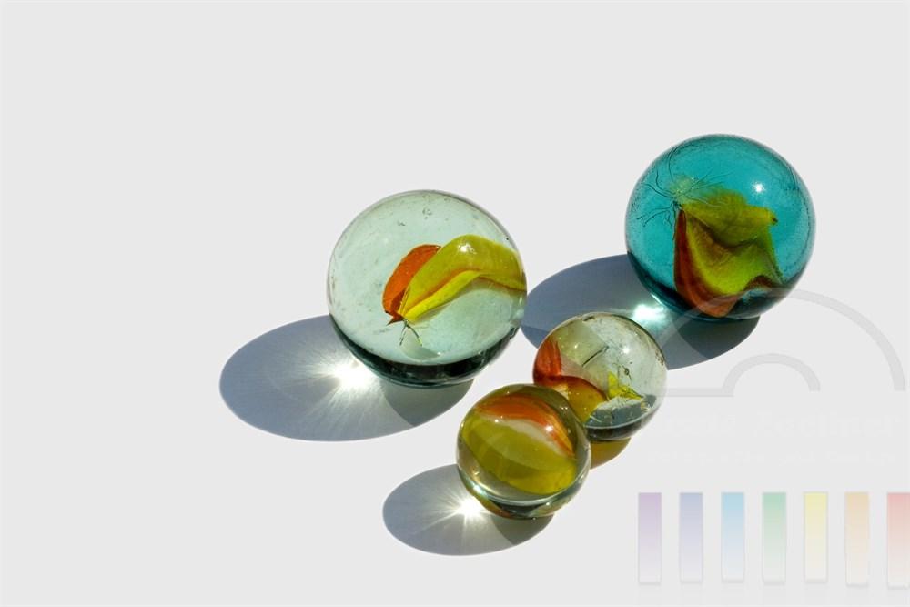 Freisteller: zwei grosse und zwei kleinere Glasmurmeln liegen gruppiert auf weissem Hintergrund, Sonnenlicht reflektiert auf der Oberfläche, die Glaskörper werfen Schatten