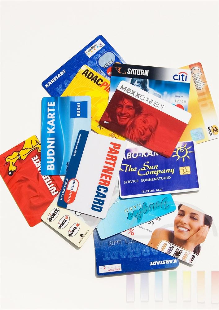 Tabletop: diverse Kundenkarten deutscher Konzerne und Großfirmen liegen unsortiert auf hellem Hintergrund