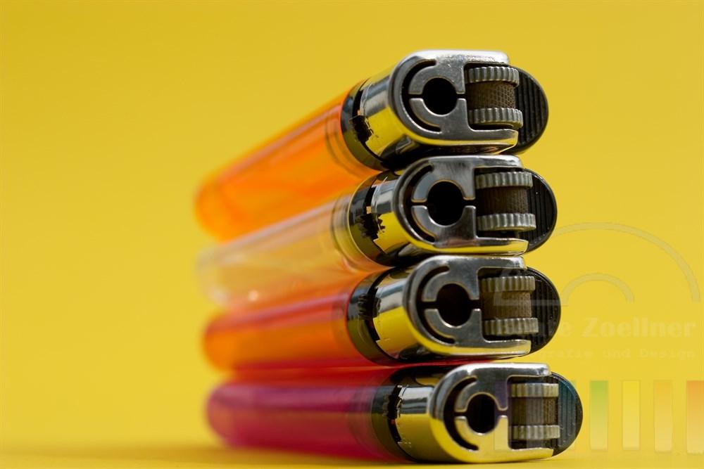 vier bunte und transparente Feuerzeuge liegen übereinander gestapelt auf gelbem Hintergrund