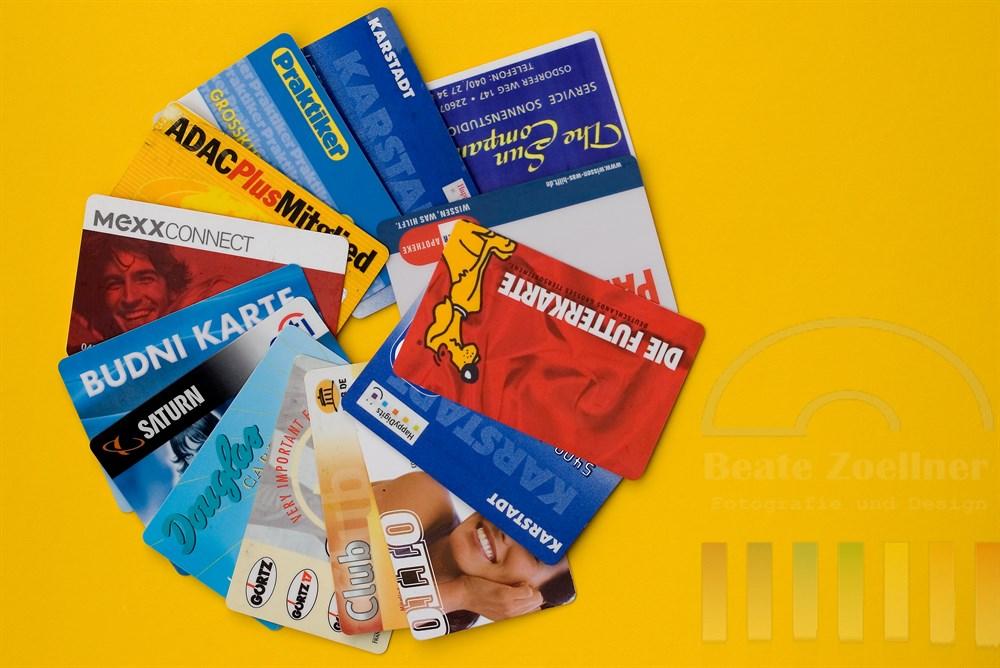 Tabletop: diverse Kundenkarten fächerförmig ausgelegt auf gelbem Hintergrund