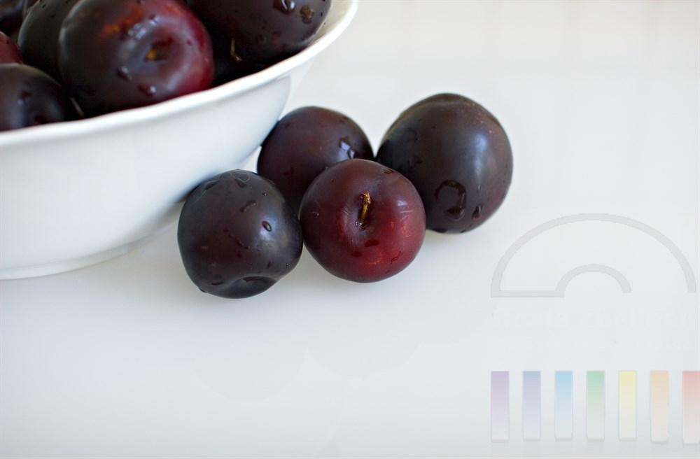 Tabletop: frische runde Pflaumen in einer weissen Schüssel und davor liegend auf weißem Hintergrund. Das Obst ist frisch gewaschen, Tropfen haften noch auf der Haut der Früchte
