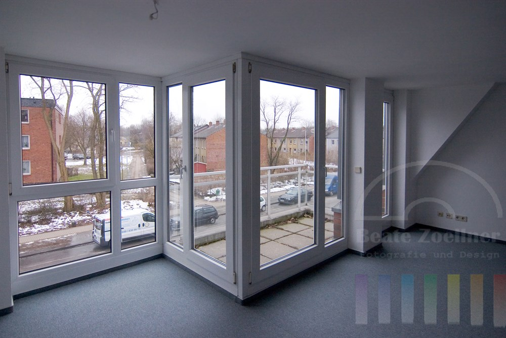 leeres Zimmer mit großen Fenstern und blauem Teppichboden. Durch die Fenster führt der Blick auf die Straße mit parkenden Autos und gegenüber stehende Wohnhäuser sowie winterlich kahle Bäume. Auf dem Boden liegt etwas Schnee.