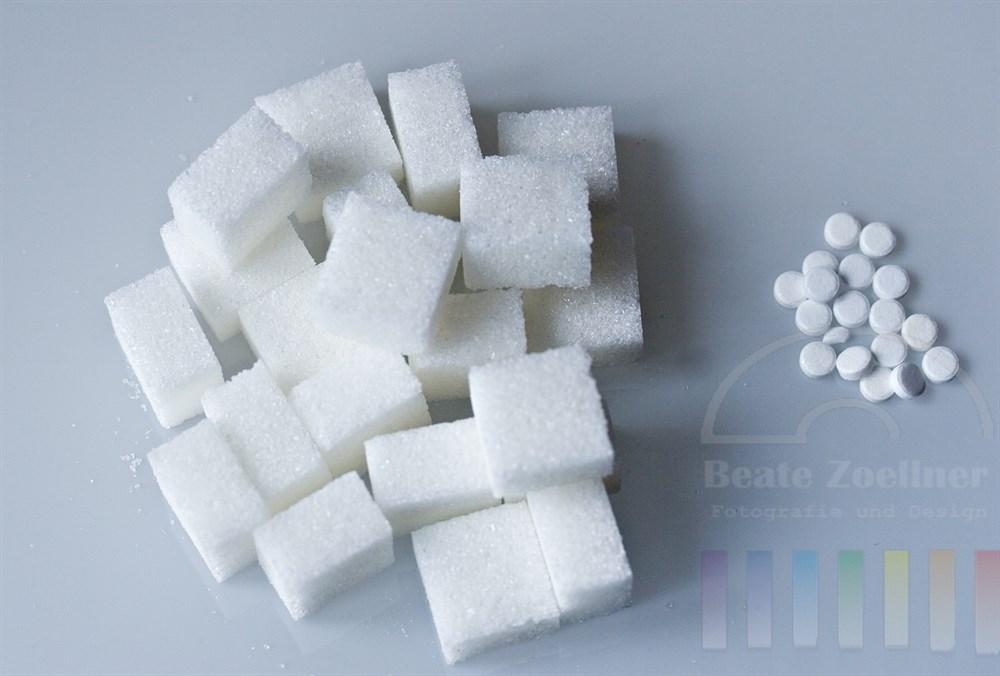 Aufsicht: mehrere Stück Würfelzucker liegen neben mehreren Süßstoff-Tabletten auf hellem Hintergrund