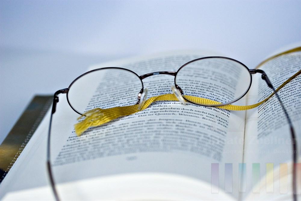 Brille liegt auf den Seiten eines aufgeschlagenen Buches, ein gelbes Band dient als Lesezeichen