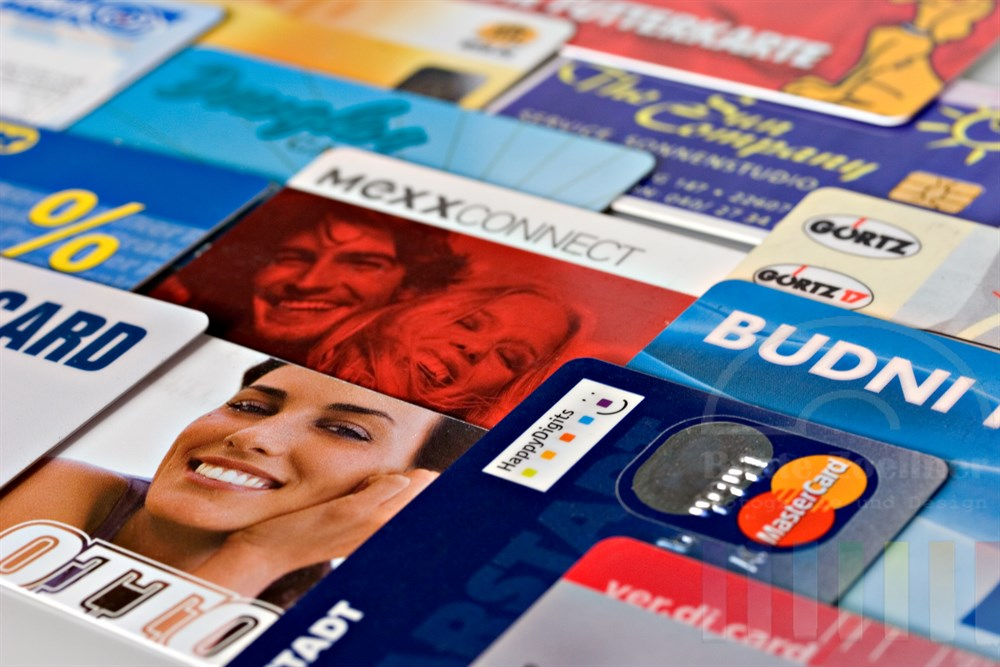 zahlreiche Kundenkarten diverser Konzerne und Filial-Betreibern liegen ausgebreitet auf hellem Hintergrund