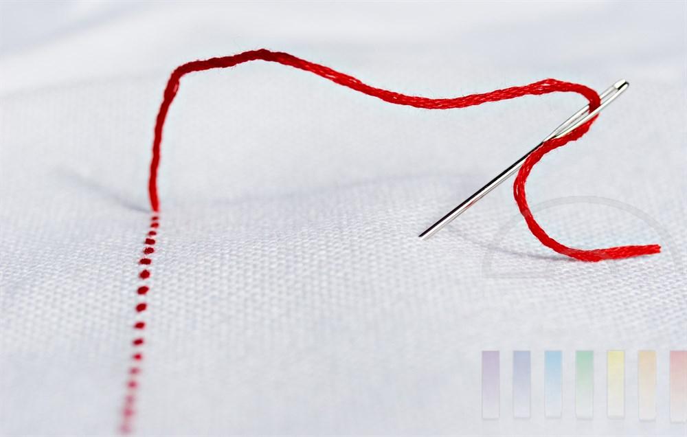 Symbolfoto: roter Faden durchzieht weisses Gewebe, ein Fadenende schlingt sich durch die Öhr einer Sticknadel