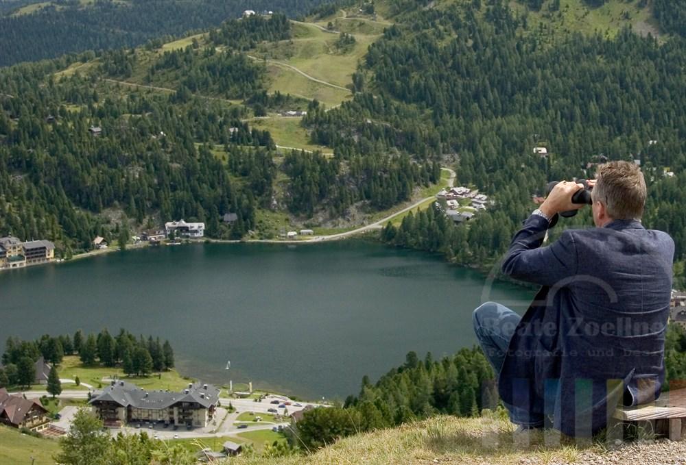 Mann (Rückansicht) sitzt auf einer Bank an einem Berghang und schaut durch ein Fernglas auf die vor ihm liegende sommerliche Berglandschaft.