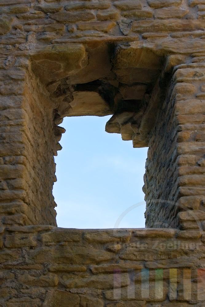 Blick durch die Fensterhöhle einer Ruine auf den blauen Himmel