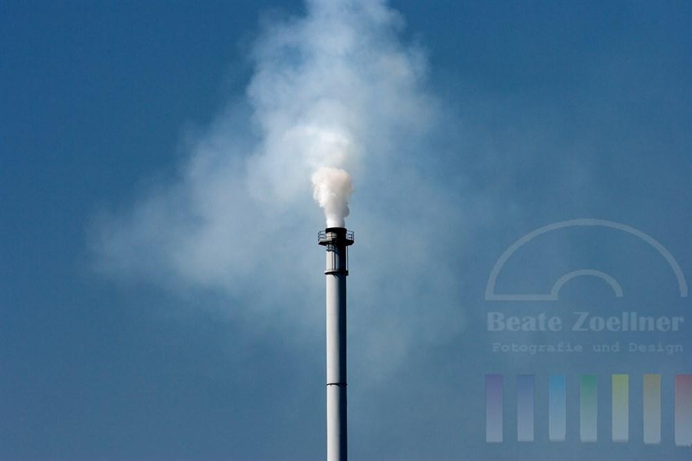 Schornstein eines Industriebetriebes bläst Abgase in den blauen Himmel